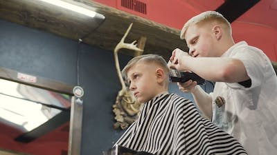 Barber with Client Child in the Barbershop