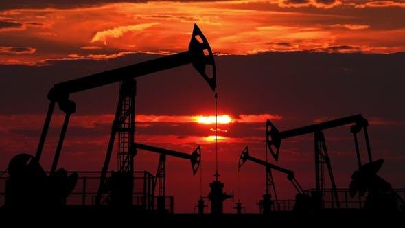 Cover Image for Oil Pumpjacks Against Red Dusk