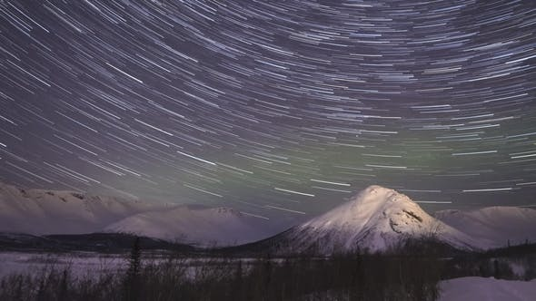 Thumbnail for Night Starry Sky with Star Trails and Green Northern Lights in Snowy Mountains at Winter Night