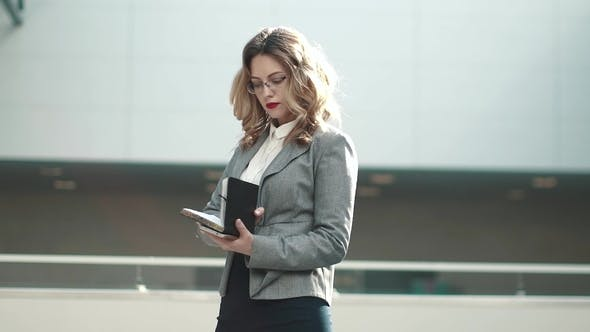 Thumbnail for Young Woman in Business Suit Looks at Notepad and Typing Message on Mobile Phone. Portrait of a