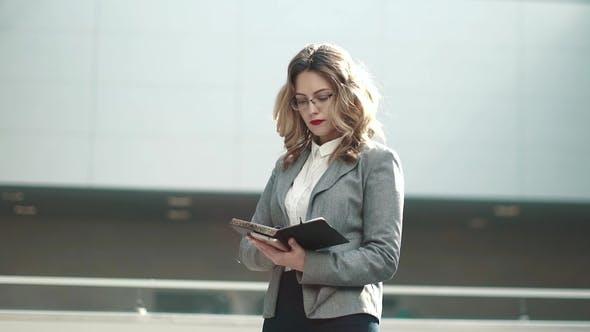 Thumbnail for Geschäftsfrau schaut sich die Notizen in ihrem Notizbuch an. mädchen in einem grau jacke in der lobby eines