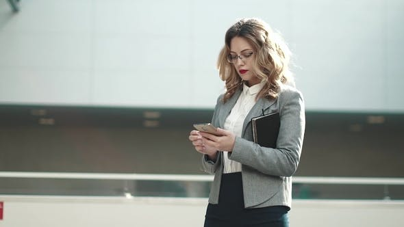 Thumbnail for Young Woman in Business Suit Typing Message on Mobile Phone. Portrait of a Business Woman in an