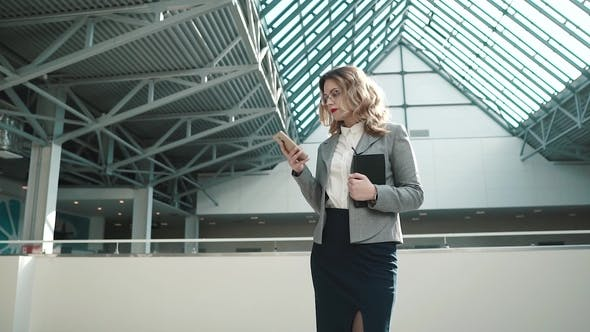 Thumbnail for Portrait of a Business Woman Using a Smartphone. Girl in Business Clothes in the Spacious Lobby of