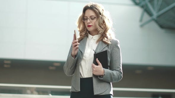 Thumbnail for Young Woman in a Business Suit Makes a Call with a Cell Phone. Portrait of a Business Woman in a