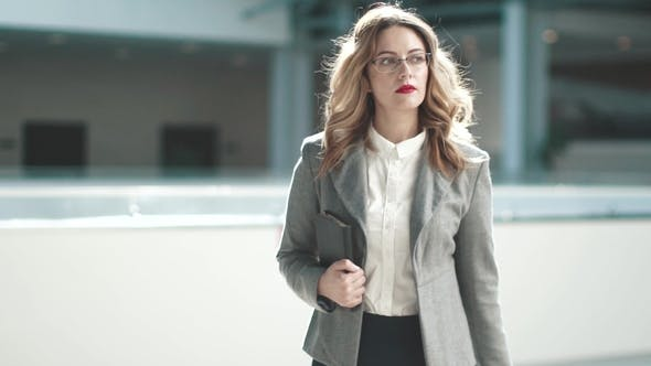 Thumbnail for a Business Woman in a Gray Jacket Goes To the Lobby of the Business Center. Girl in a Business Suit