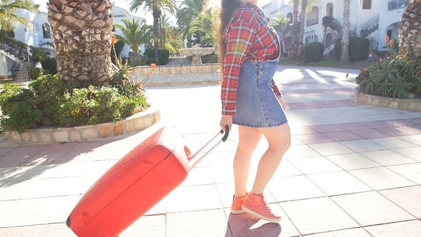 Young Woman with a Suitcase on a Resort
