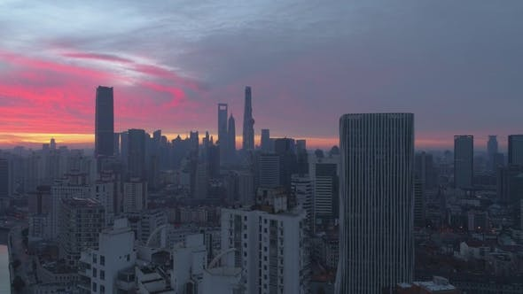 Cover Image for Shanghai Skyline at Pink Sunrise. Panoramic Aerial View. China. Drone Is Flying Upward and Sideways