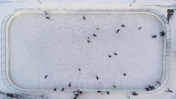Cover Image for People Are Skating on Ice Rink in the Sunny Day. Aerial Vertical Top-Down View