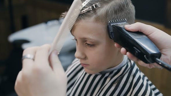 Thumbnail for Hairdresser with Cute Client Child in the Barbershop Barber Using Trimmer and Comb in Barbershop