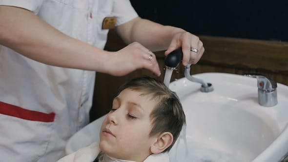 Thumbnail for Image of Stylish Male Barber Washing Hair of His Little Client for Making Modern Haircut
