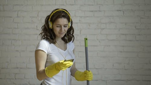 Happy Woman in Headphones Singing, Pretending To Mop the Microphone, Amid the White Brick Wall