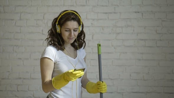 Thumbnail for Happy Woman in Headphones Singing, Pretending To Mop the Microphone, Amid the White Brick Wall