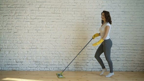 A Dancing Young Woman Cleaning a Woman in Yellow Gloves Laughs, Holds a Mop in Her Hands