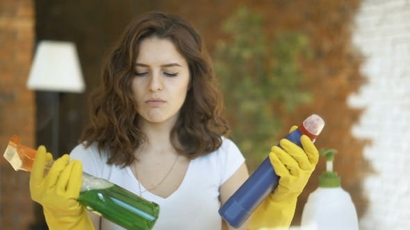 Woman Comparing Spray Detergent Products, She Is Holding Two Bottles and Checking Them
