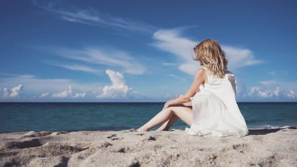 Thumbnail for A Girl Sits on the Sand and Sunbathes