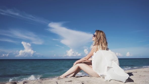 Thumbnail for A Girl Sits on the Sand and Sunbathes.