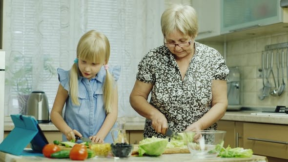 Cover Image for Cook Together. The Girl of 6 Years Helps Her Grandmother in the Kitchen, Watching the Salad Recipe