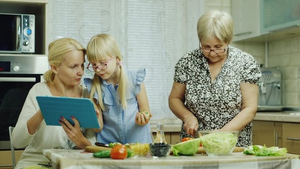 Thumbnail for Grandmother, Mother and Granddaughter Cook Together a Salad in the Kitchen. Enjoy a Tablet, Have a