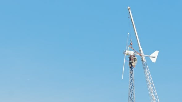 Cover Image for Hazardous Work at Height. Workers Repairing Wind Turbine. High Up on a Background of Blue Sky and