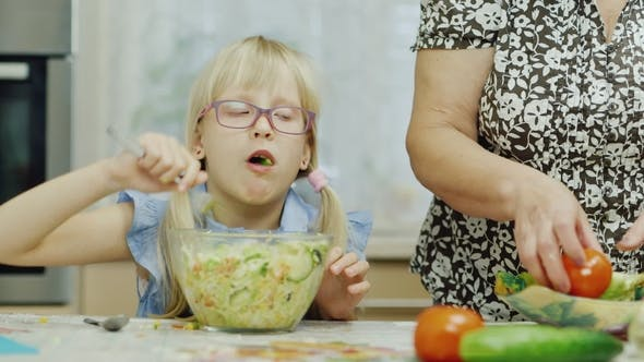 Thumbnail for Granddaughter Visiting Grandmother. A 6 Year Old Girl Eats a Salad. Next To Her, an Elderly Woman