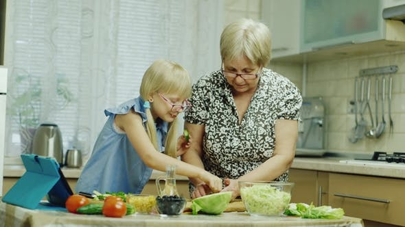 Cover Image for Grandmother Teaches Her Granddaughter To Prepare a Salad, Use a Tablet. Together Have a Good Time