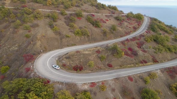 Thumbnail for White Crossover Car Goes on Serpentine Mountain Road