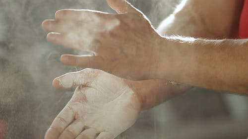 Weight Lifter Bodybuilder Smears His Hands with Magnesium