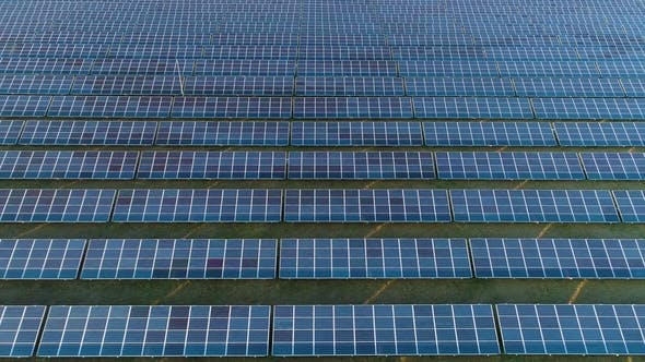 Cover Image for Large Field of Blue Photovoltaic Solar Panels. Aerial View. Flying Sideways To the Right
