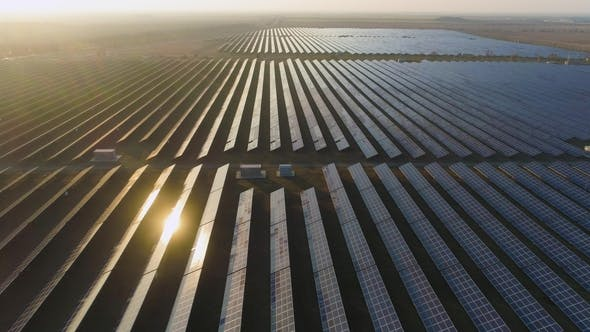 Thumbnail for Large Field of Photovoltaic Solar Panels at Sunset. Sunlight Reflection. Aerial View. Flying Forward