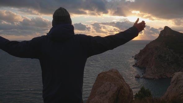 Thumbnail for Silhouette of Man in Jacket and Cap Standing with Raised Hands and Looking at Sunset