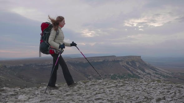 Thumbnail for Young Hiker Woman with Backpack and Hiking Poles Is Walking Along the Edge of Rock