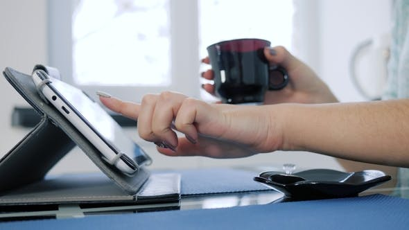 Thumbnail for Using Tablet During Morning Coffee in Woman's Hand on Unfocused Background