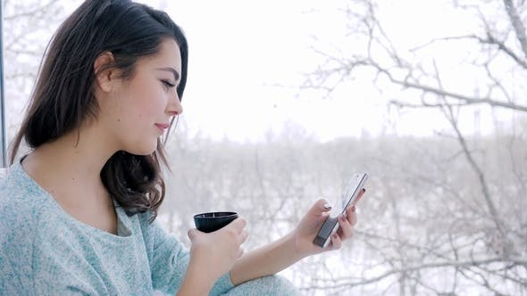 Thumbnail for Beautiful Girl Sitting on Internet Using Smartphone and Drinking Tea at Home near Large Window