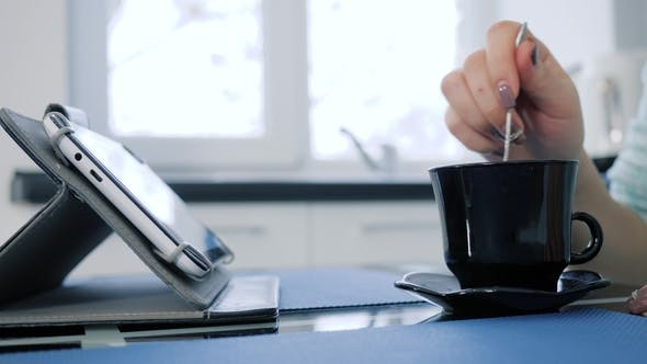 Thumbnail for Female Hand with Spoon Mixes Tea in Cup and Clicks in Tablet on Unfocused Background