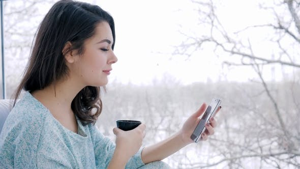 Cover Image for Smiling Female Spends Time on Internet on Mobile Phone and Drinking Tea Sitting near Large Window