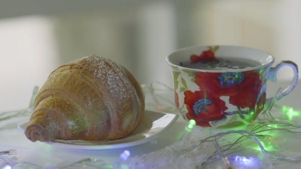 Thumbnail for Hot Steaming Tea with Croissant Decorated with Blinking Garland on Table