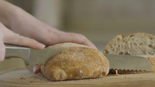 Frau schneidet Brot in auf Schneidebrett