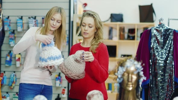 Cover Image for Two Young Women Choose a Warm Cap in the Store. Winter Shopping