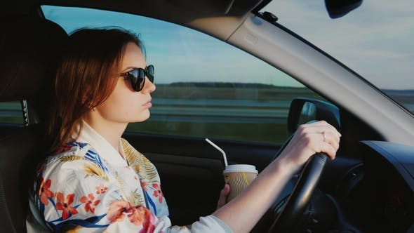 Cover Image for Fragrant Coffee on the Road. Young Stylish Woman Drinks Coffee, Drives Car on Highway