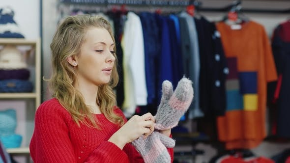 Thumbnail for Winter Shopping. Young Woman Trying on Warm Gloves in a Clothing Store