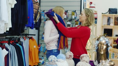 Pleasant Shopping. Two Female Friends Choose Warm Clothes, Try on Their