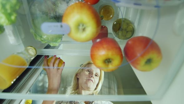Thumbnail for Easy Fruit Snack. A Hungry Woman Opens the Fridge, Takes an Apple and Eats. View From Inside the