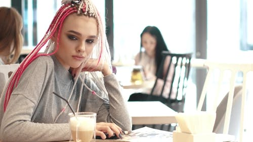 Girl with Dreadlocks in a Cafe. a Teenager with an Unusual Appearance. Subculture of