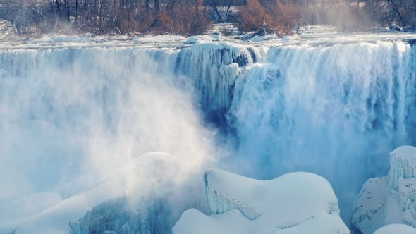 Cover Image for Winter Season at Niagara Falls. The Sun's Rays Illuminate the Fog and Splashes From the Waterfall