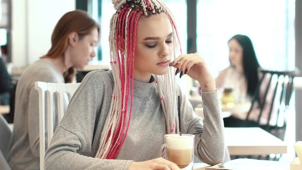 Thumbnail for Portrait of a Teenager with Dreadlocks in a Coffee House. Girl with Unusual Appearance