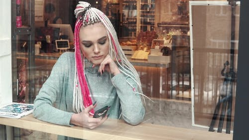 Portrait of a Girl with Dreadlocks in a Cafe. a Teenager with an Unusual Appearance. Subculture of