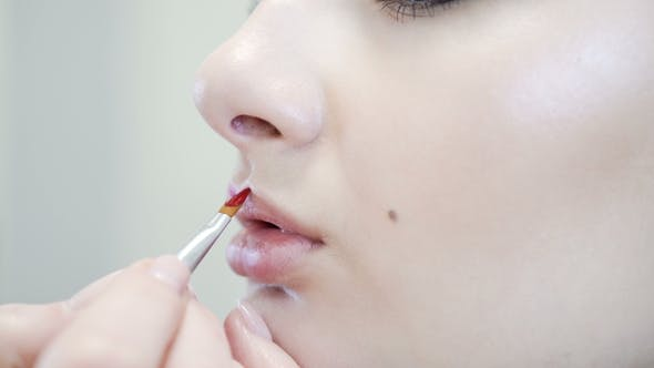 Thumbnail for of an Attractive Beauty Girl Doing Full Make-up. Woman Applying Red Lip