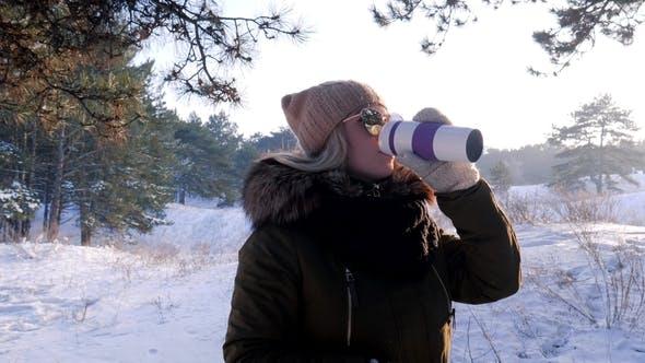 Thumbnail for Junge Frau trinken heißen Tee oder Kaffee aus der Tasse im Freien im Winter Wald im Freien