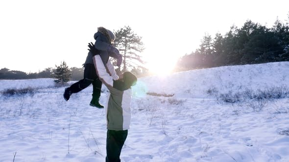 Thumbnail for Happy Daddy Throwing up His Little Boy into Air and Have Fun Time Together at Winter