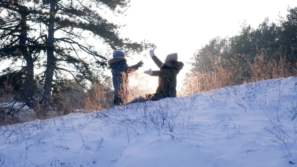 Cover Image for Mother Playing with Son on Snow in Backlight at Forest